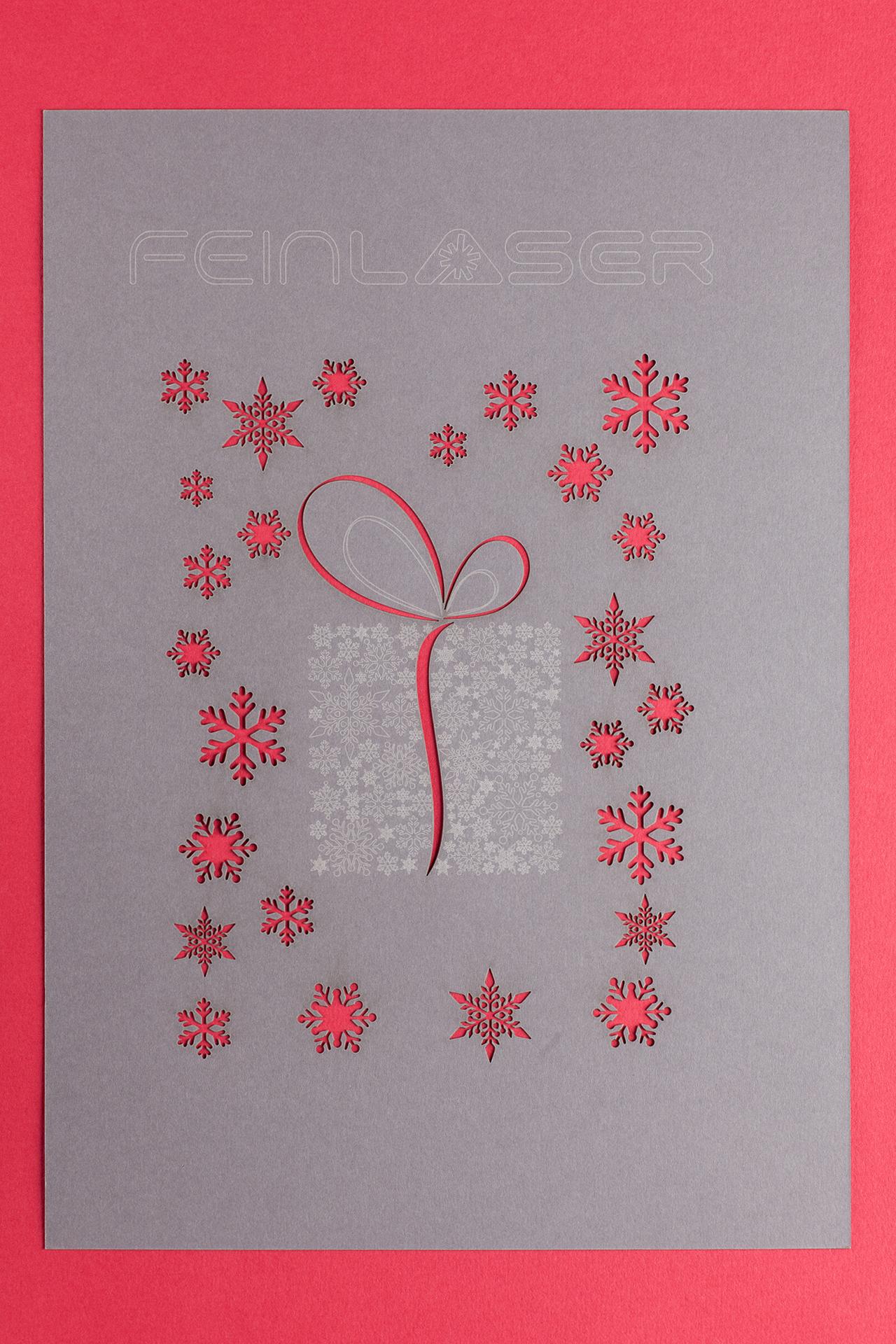Schneeflocke und Geschenk laser geschnitten aus Papier