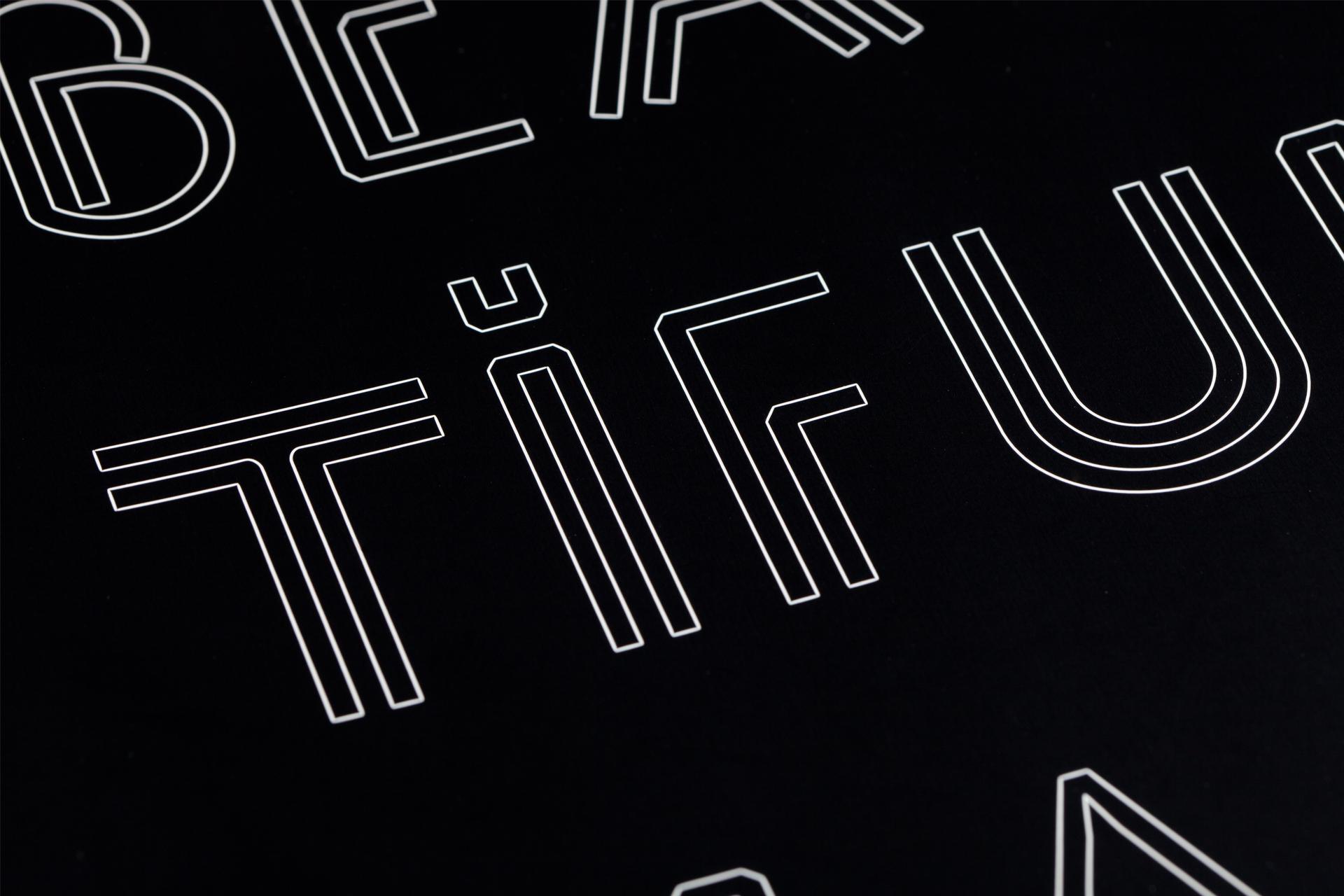 Lasergravierter Schriftzug weiß auf schwarz